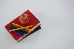 Apple ed il colore disegnano a matita sul libro su fondo bianco Fotografie Stock Libere da Diritti