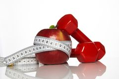 Apple ed il rosso hanno colorato le teste di legno legate con nastro adesivo di misurazione Immagini Stock