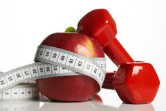 Apple ed il rosso hanno colorato le teste di legno legate con nastro adesivo di misurazione Fotografie Stock