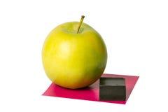 Apple, ein Stück der Schokolade und des Quadrats des Papiers Stockfotografie