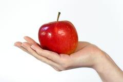 Apple in einer Hand Lizenzfreies Stockfoto