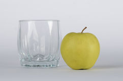 Apple with empty glass. Green apple with empty glass on white background Stock Photos