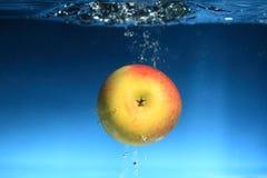 Apple en el agua salpica sobre fondo azul Imagen de archivo