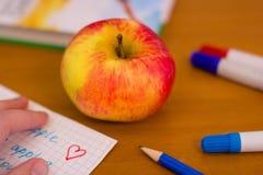 Apple en el escritorio de la escuela Foto de archivo libre de regalías