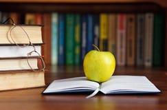 Apple en el libro abierto Imagen de archivo libre de regalías