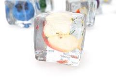 Apple en glaçon d'isolement sur le blanc avec la profondeur des effets de champ Glaçons avec les baies fraîches Baies congelées d Images stock
