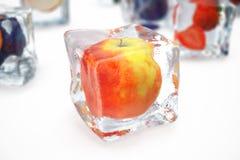 Apple en glaçon d'isolement sur le blanc avec la profondeur des effets de champ Glaçons avec les baies fraîches Baies congelées d Photos stock