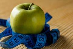 Apple en het meten van band op een lichte bamboelijst Stock Fotografie