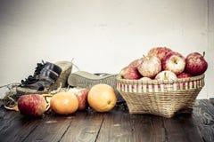 Apple en la cesta de bambú y naranjas en la tabla de madera Fotografía de archivo