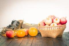 Apple en la cesta de bambú y naranjas en la tabla de madera Imagen de archivo libre de regalías