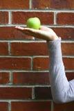 Apple en la mano con el fondo del ladrillo. Fotografía de archivo