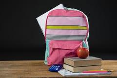 Apple en la pila de libros con el bolso de la calculadora y de escuela Imagen de archivo libre de regalías