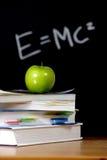 Apple en la pila de libros en sala de clase Fotografía de archivo libre de regalías