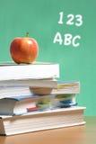 Apple en la pila de libros en sala de clase Foto de archivo libre de regalías