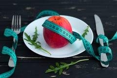 Apple en la placa con la cinta métrica en el fondo de madera Imágenes de archivo libres de regalías