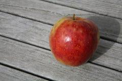Apple en la tabla de madera Imagen de archivo libre de regalías