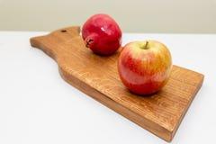 Apple en rijpe granaatappel aan boord van geïsoleerd op witte achtergrond Samenstelling van rode vruchten en rustiek gevolg Eco royalty-vrije stock fotografie
