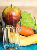 Apple en un vidrio vacío con bróculi, la zanahoria y los plátanos Foto de archivo
