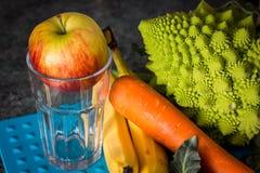 Apple en un vidrio vacío con bróculi, la zanahoria y los plátanos Fotografía de archivo libre de regalías