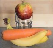 Apple en un vidrio vacío con los plátanos y la zanahoria Foto de archivo