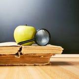 Apple en vergrootglas over de boeken Royalty-vrije Stock Fotografie