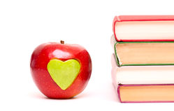 Apple engraved with a heart and stack of books Stock Photography
