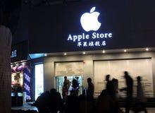 Apple entreposé en Chine étant fermée avec des silhouettes des passants Photos stock
