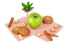 Apple, Erdnüsse und Hafermehlplätzchen auf einer weißen Tabelle Stockfotografie