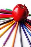 Apple et crayons colorés sur le fond blanc Image stock
