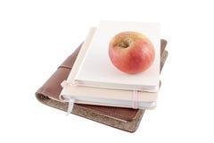 Apple et livres sur un fond blanc Photographie stock libre de droits