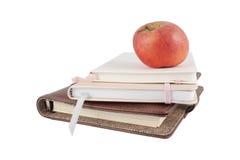 Apple et livres sur un fond blanc Photographie stock