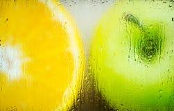 Apple et orange dans un verre givré images stock