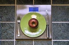 Apple et plat placé sur l'échelle de poids Image stock