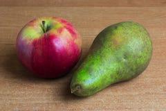 Apple et poire sur la table Photos libres de droits