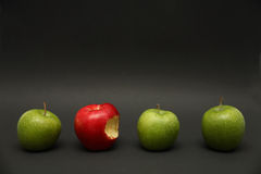 Apple Exception. A line of apples with one exception Stock Photo