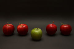Apple Exception. A line of apples with one exception Stock Photos