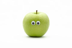 Apple face. Green apple with googly eyes on white background - portrait royalty free stock image