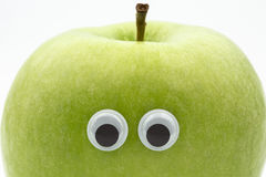 Apple face. Green apple with googly eyes on white background - portrait Stock Images