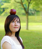Apple fall on head. Beautiful young Asian woman with red apple on her head Royalty Free Stock Photography