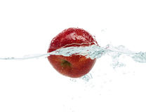 Apple falling or dipping in water with splash. Fruits, food and healthy eating concept - close up of fresh apple falling or dipping in water with splash over stock image