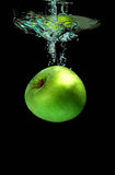 Apple falling into water. Green apple falling into water royalty free stock images
