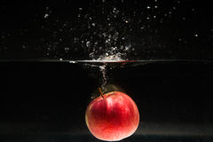 Apple falling in water Royalty Free Stock Image