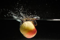 Apple falling in water Stock Photo