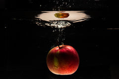 Apple falling in water Royalty Free Stock Photos