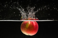 Apple falling in water. With black background stock images