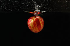 Apple falling into the water with a splash. On a dark background closeup Stock Image