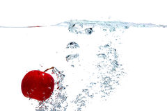 Apple falls deeply under water. Fresh red apple falls deeply under water with a splash isolated on white background Royalty Free Stock Photo