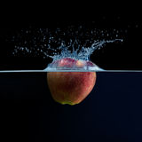 Apple falls into the water. Water splash Royalty Free Stock Image