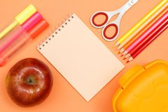 Apple, felt pens, notebook, scissors, color pencils and lunch bo. X on pink background. Top view with copy space. Back to school concept. School supplies. Pastel stock photos