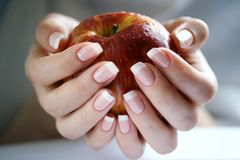 Apple in a female hand Royalty Free Stock Images